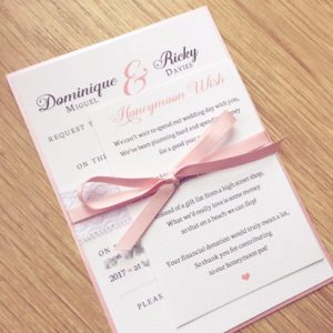 Blush pink wedding invitation with delicate lace and ribbon