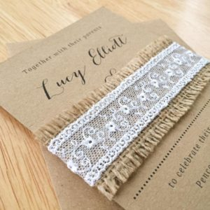 Simple, rustic wedding invitation bundles held together with hessian and lace.