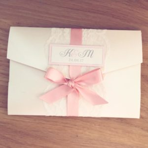 Pearlescent pocketfold invitations with wide lace and a blush pink bow