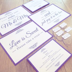 Signs, menus and favour tags with purple glittery borders and silver gems