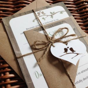 Rustic wedding invitations bundles with wood effect background and love birds on a branch. Finished with twine and a paper cut tag