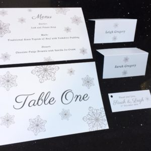 Pearlescent white table names, menus, place cards and favour tags with snowflakes and gems
