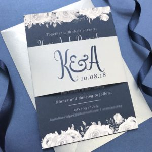 Navy invitations with grey roses and a silver belly band
